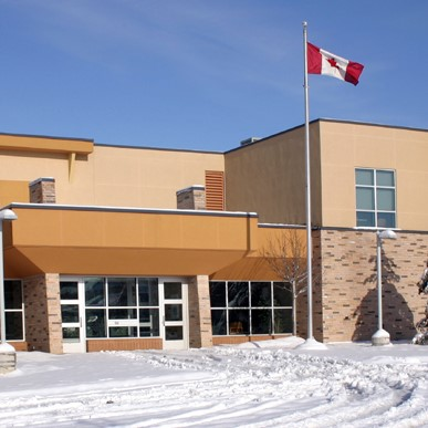 School building with Canadian flag in front on a snowy day