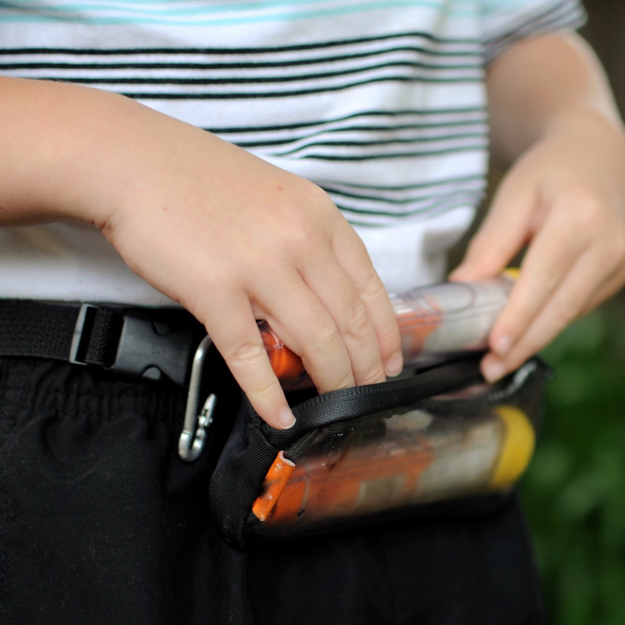 Two anaphylaxis Auto injectors in small pouch. Carry case is being worn by a child who is removing one injector from the case.