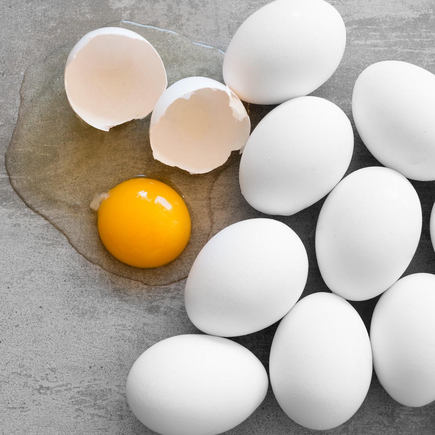 White eggs, one broken egg showing yolk