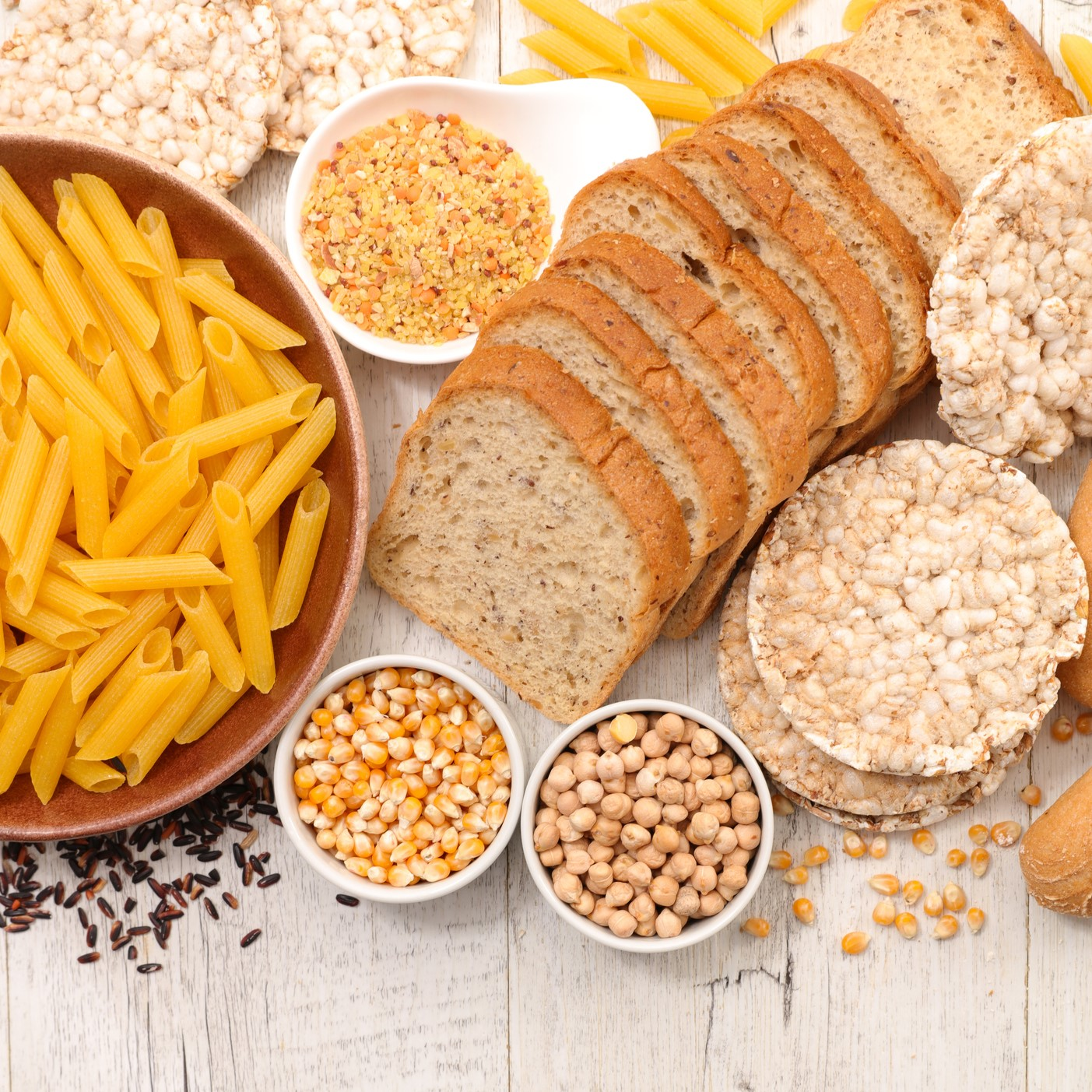 Products containing gluten on wooden table, including pasta, bread, and rice cakes.