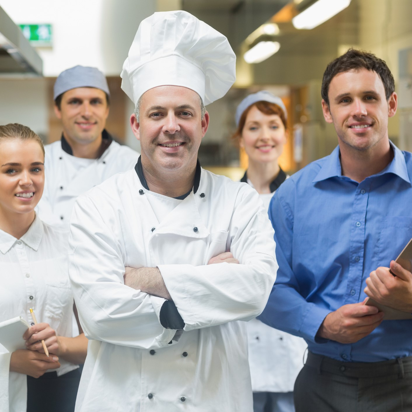 Head chef posing with the team behind him in a profesional kitchen