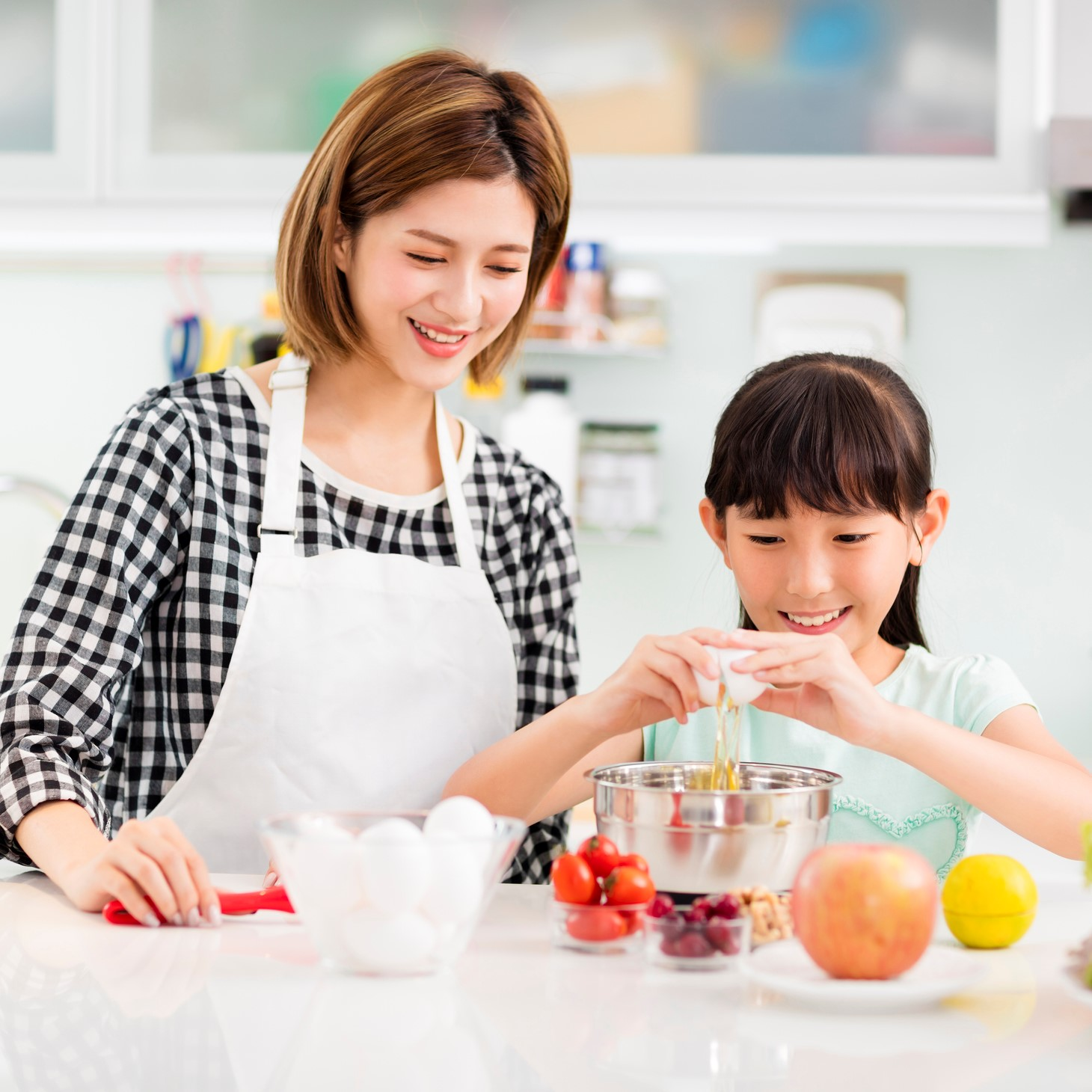 Mother and child in kitchen preparing cookies