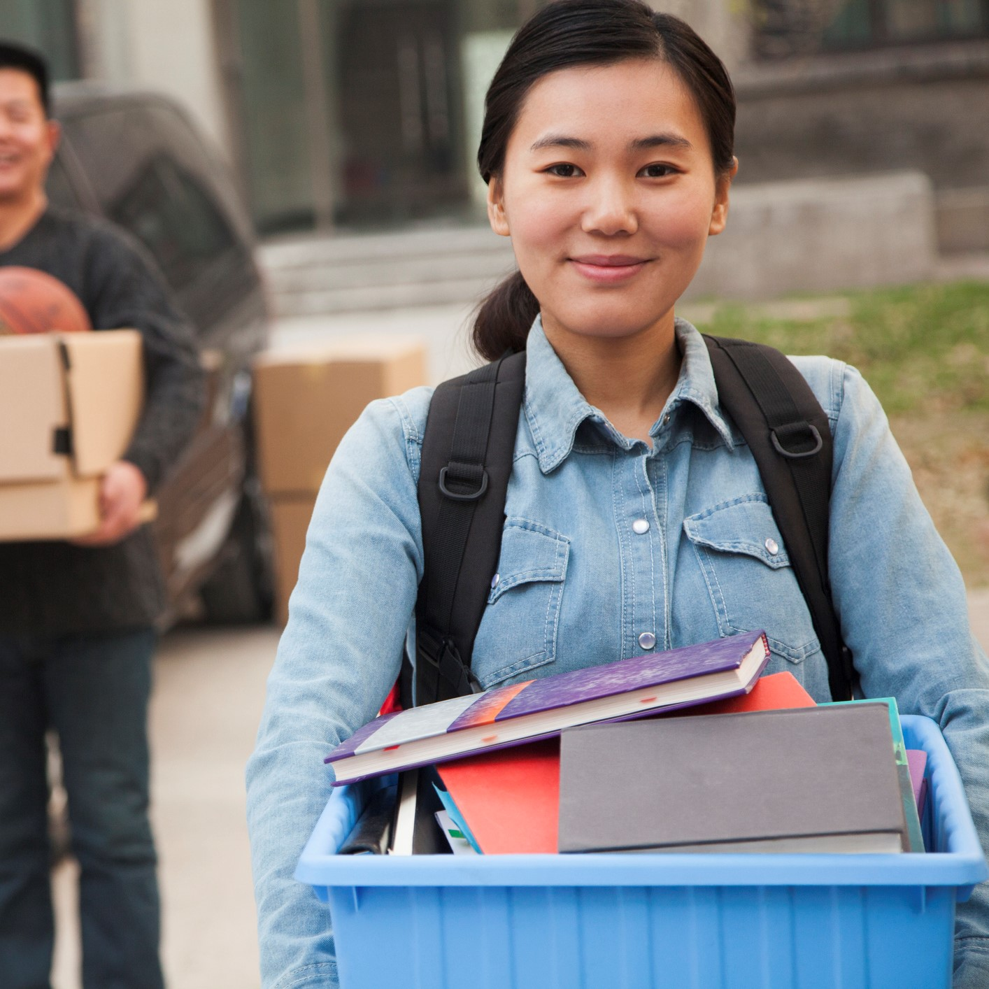 Student in front of a dorm, moving in and carrying a box of books