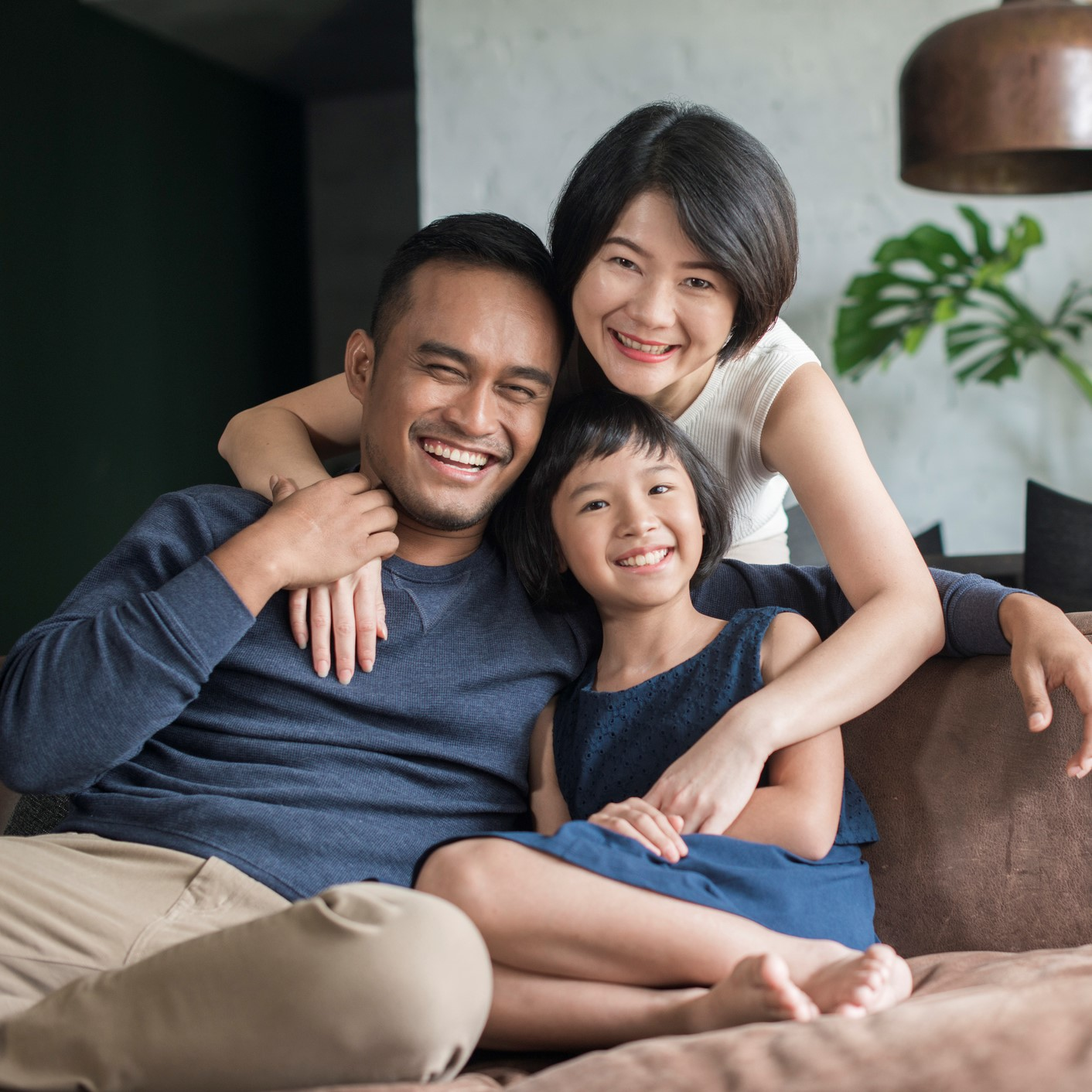 Young parents with only child relaxing on the sofa in the living room.